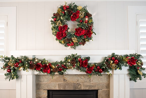 Red Magnolia Wreath and Garland Hanging Above Fireplace Mantle