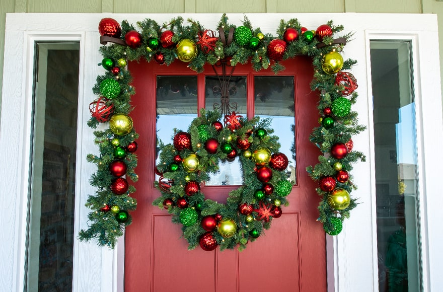 Festive Holiday Wreath and Garland Hanging On Front Door