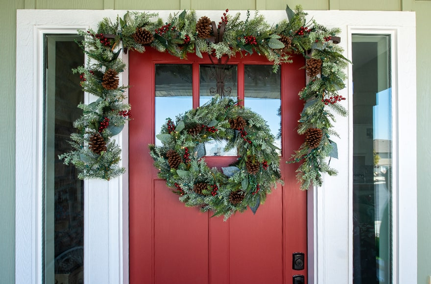 Winter Frost Wreath and Garland Hanging On Front Door