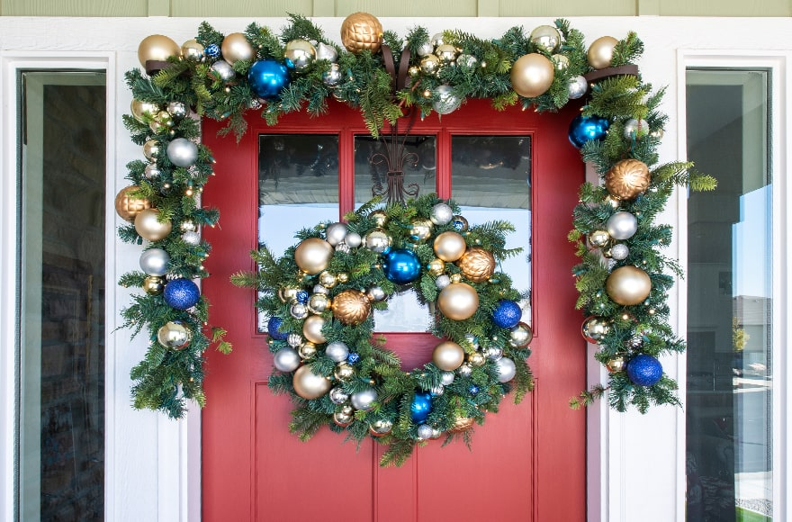 Celebration Ornament Wreath and Garland Hanging On Front Door
