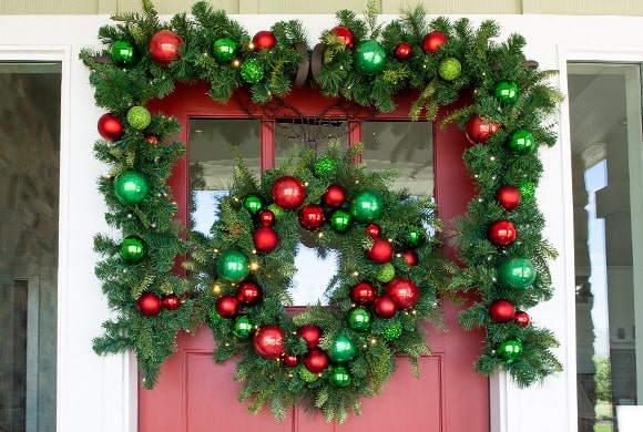 Christmas Cheer Red and Green Wreath and Garland Hanging On Front Door