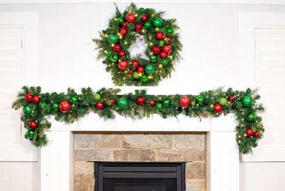 Christmas Cheer Red and Green Wreath and Garland Hanging Above Fireplace Mantle