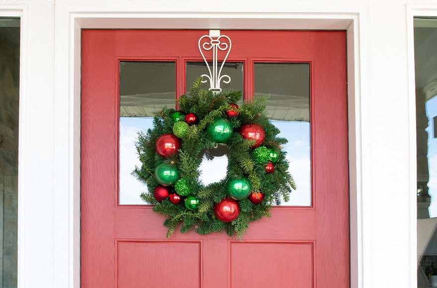 Christmas Cheer Red and Green Wreath Hanging On Front Door