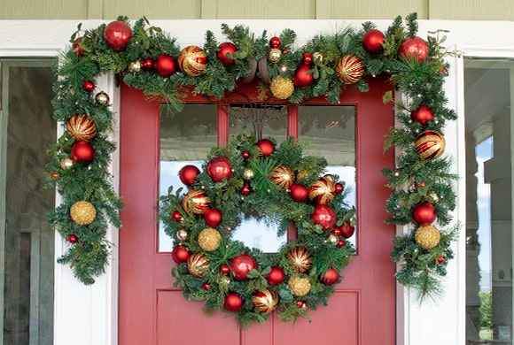 Christmas Classic Red and Gold Wreath and Garland Hanging On Front Door