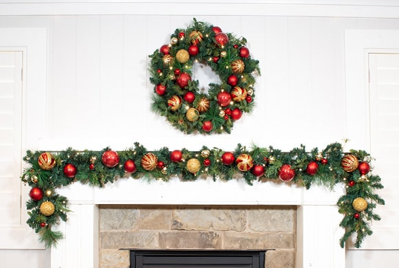 Christmas Classic Red and Gold Wreath and Garland Hanging Above Fireplace Mantle