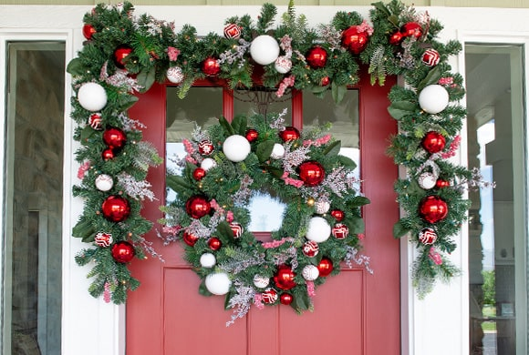 Nordic Red and White Wreath and Garland Hanging On Front Door