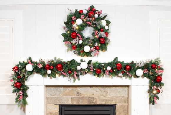 Nordic Red and White Wreath and Garland Hanging Above Fireplace Mantle