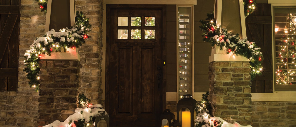 Village Lighting Company Christmas Garlands  with C7 lights wrapped around house porch pillars