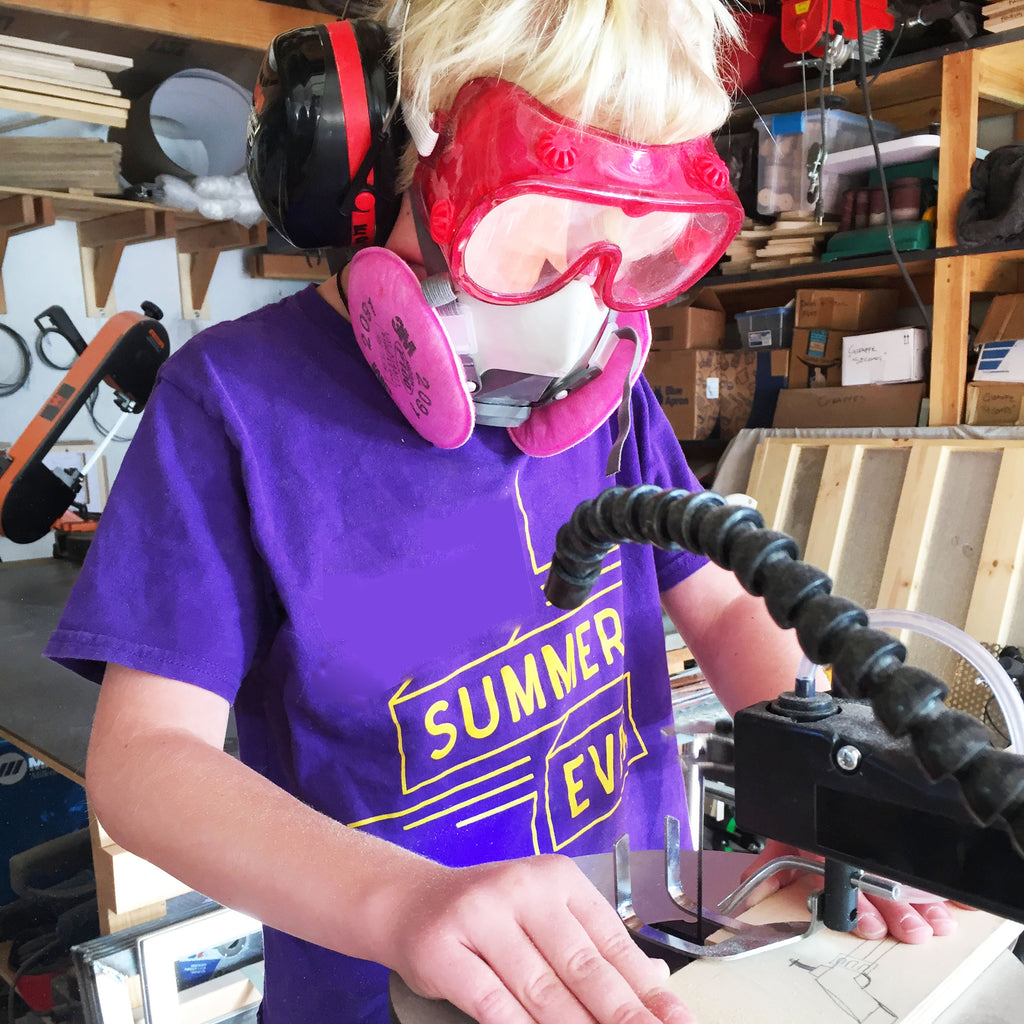 Image of a young blond boy cutting wood on a scroll saw.  The boy is wearing red safety goggles, a respirator with pink P100 filters, and large hearing protection