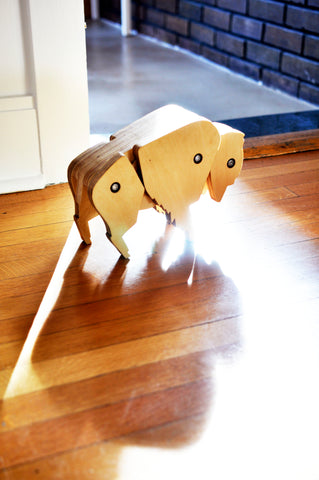 Image of an Eric Jacoby Tectonic Bison walking across a wooden floor and casting a long dramatic shadow behind her.