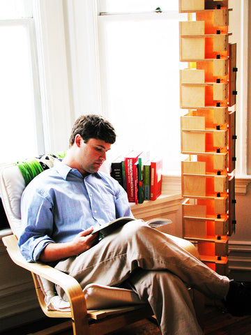Image of a man (Eric Jacoby) reading in an armchair next to a tall, modular lamp