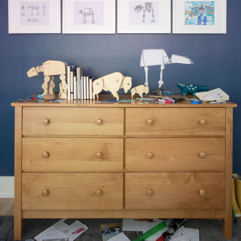 a wooden dresser with wooden Star Wars AT-AT and wooden bison