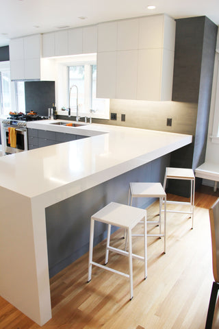 Image of a modern kitchen with white counters, white cabinets, white Eric Jacoby Tectonic Stools and a bright window over the kitchen sink.