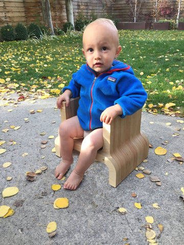 Image of a young boy sitting in an Eric Jacoby Design Upend Chair on an outdoor patio. Fall leaves are scattered on the ground around him