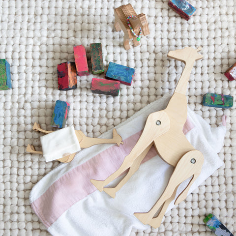 Tectonic Giraffe Family lying on the floor and covered with doll blankets