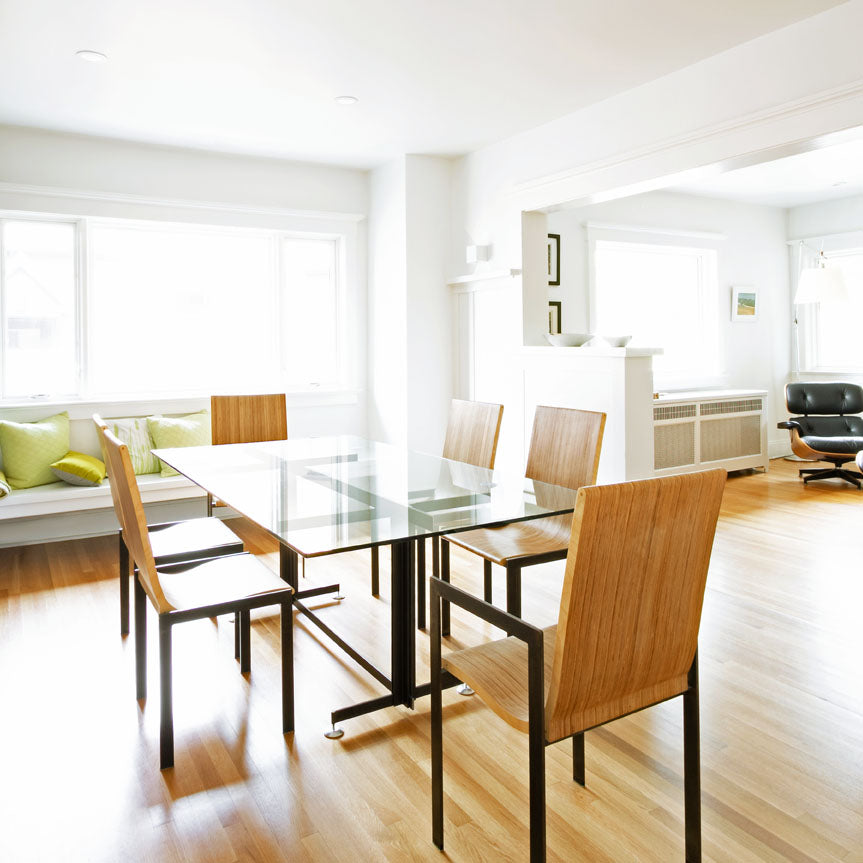 Image of bright dining room with modern steel and glass dining table surrounded by modern wood and steel dining chairs