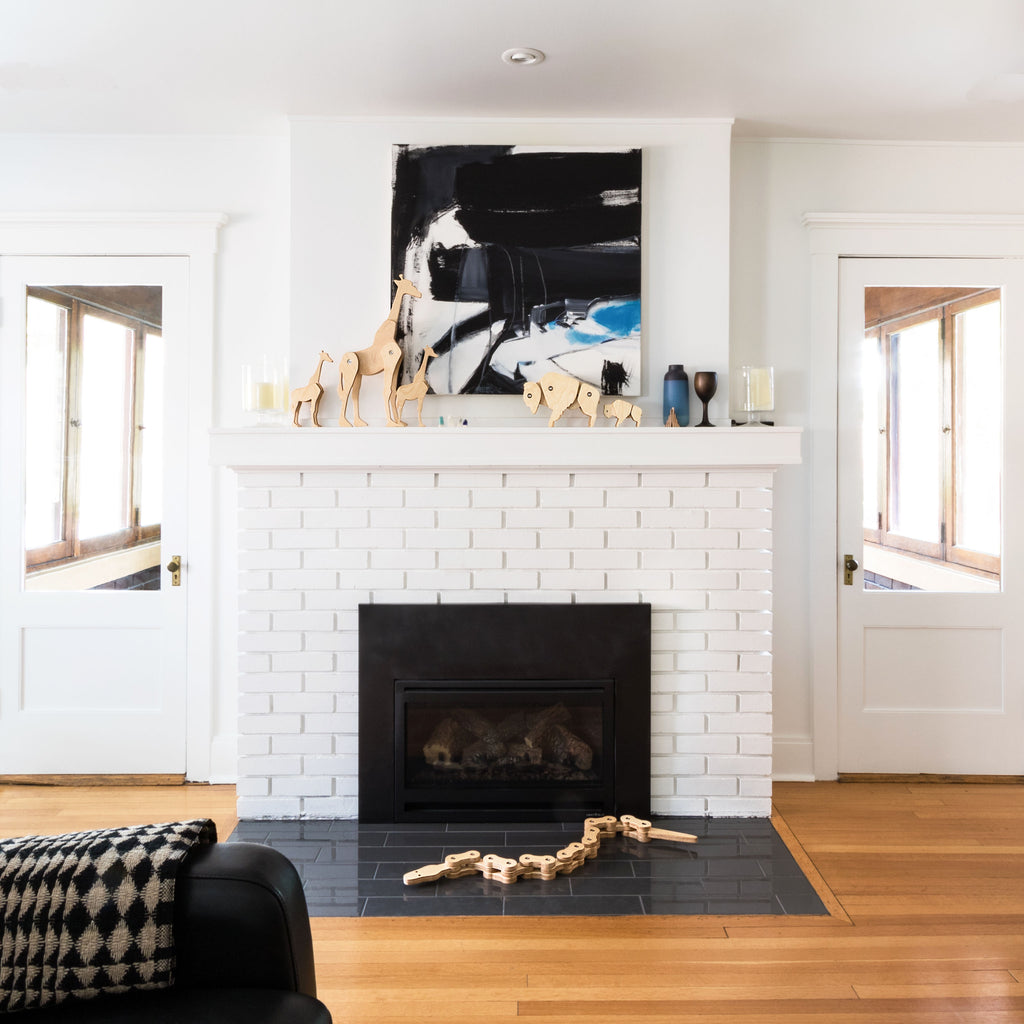 Modern white living room with Tectonic Giraffe family and Tectonic Bison Family on a white mantle in front of a modern painting, and the Tectonic Chain Snake on the grey tile hearth