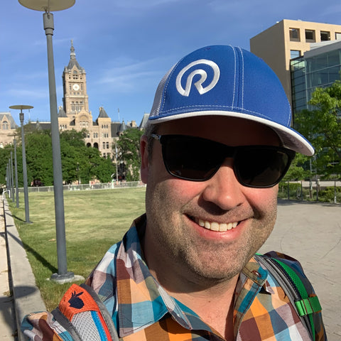Image of a man (Eric Jacoby) wearing a hat and sunglasses standing 100 yards in front of the Salt Lake City and County Building