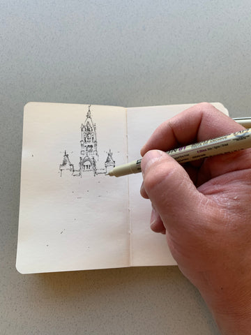 Image of a hand being supported by one side of a sketchbook, while drawing a building on the opposite page