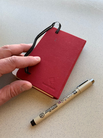 Image of a mans left hand holding the corner of a small, red travel sketchbook