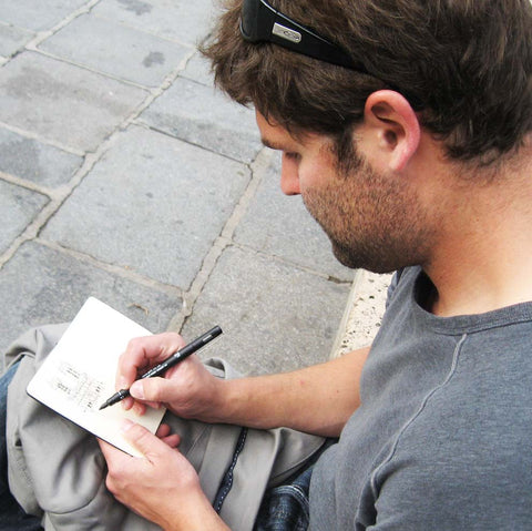 Image of a man (Eric Jacoby) sitting on a low concrete wall with a blazer in his lap, sketching Notre Dame Paris in a small travel sketchbook