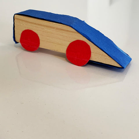 simple home made car made from a scrap wood and colored construction paper