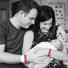 couple wearing washmind reminder bracelets while holding their new baby