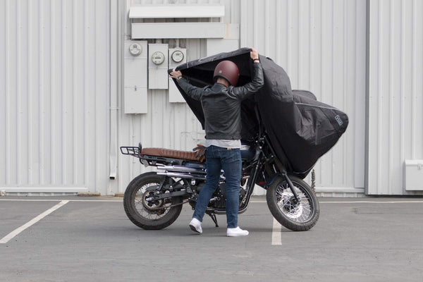 Rider putting Vuz Moto motorcycle cover on a motorcycle