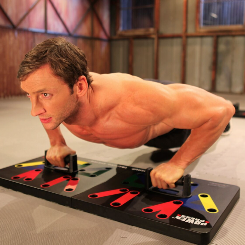 Man using the Power Press push up board in a gym setting