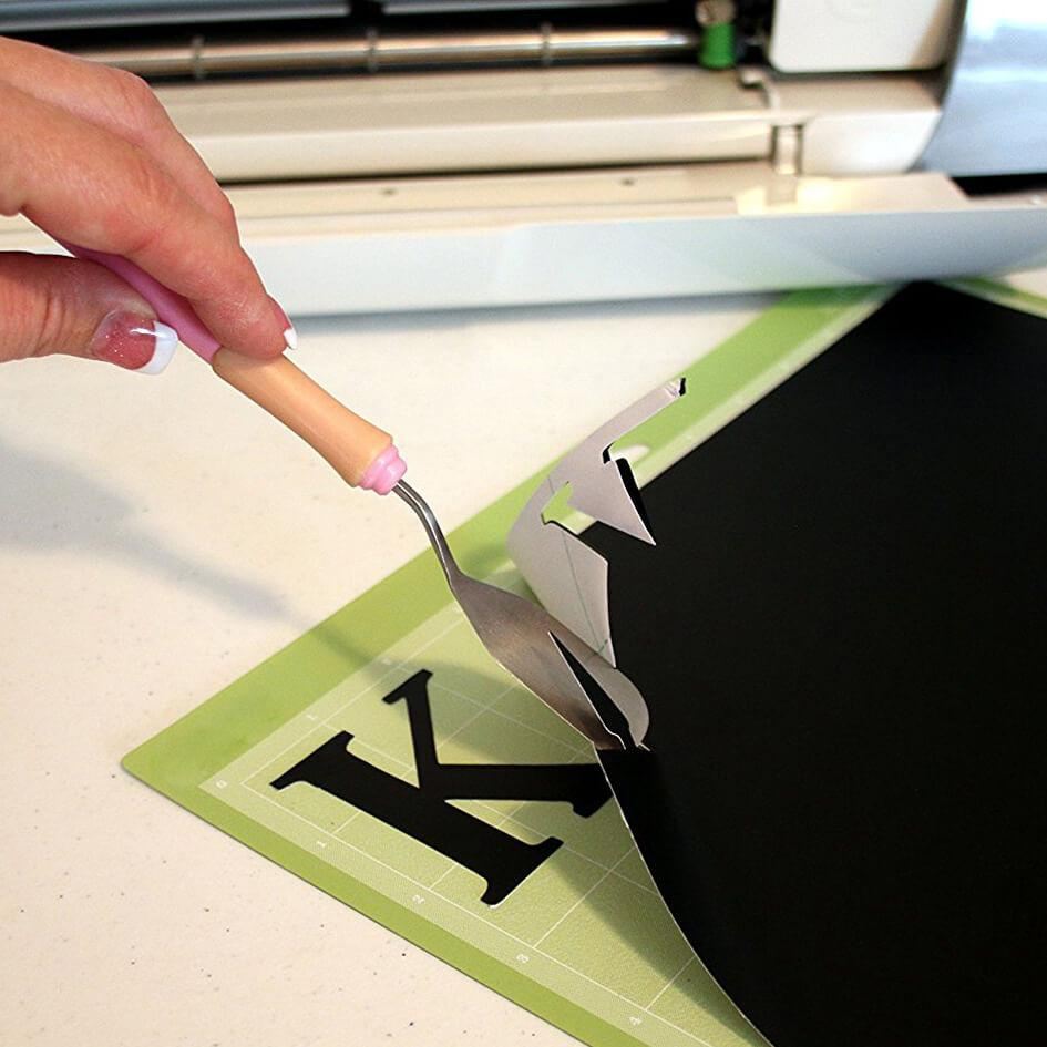Black Matte vinyl sheet with hand holding a weeding tool after cutting out the letter K