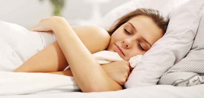 young woman sleeps on her side in white bed