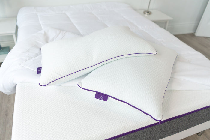 two queen size white pillows on white memory foam mattress