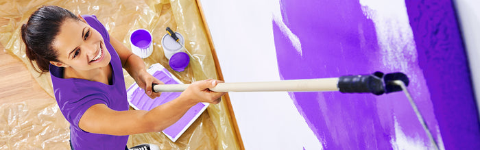 woman paints bedroom walls in purple