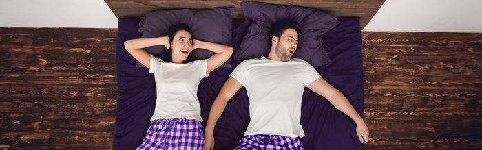 woman covers ears lying next to man snoring loudly due to sleep apnea