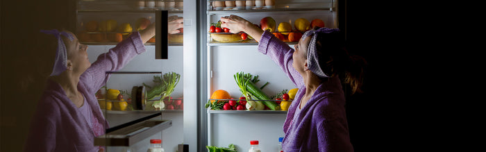 woman reaches for fruits and vegetables from inside of fridge door