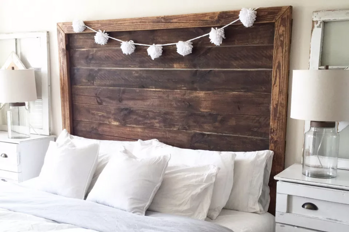 large rustic, wooden headboard behind queen size mattress with white bedding