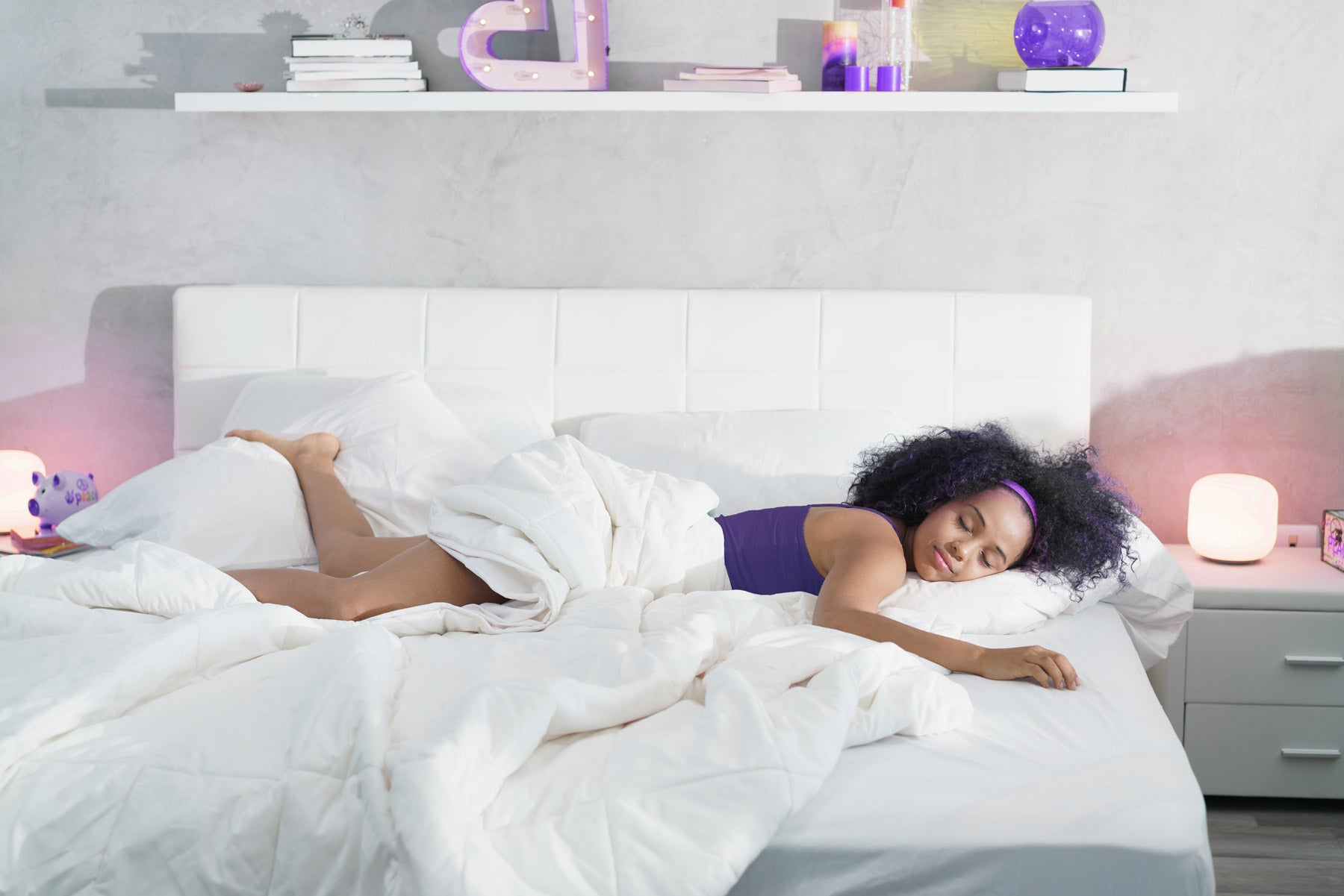 woman in purple tank top sleeps sideways on bed with white sheets