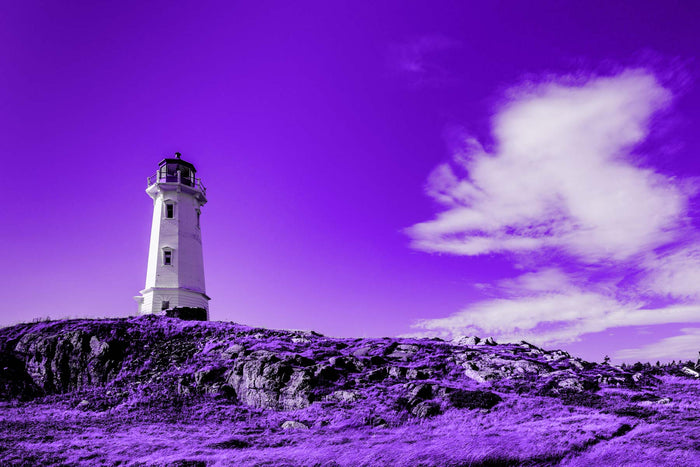 lighthouse on rocky landscape in front of white clouds