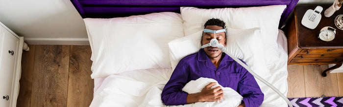 man in purple PJs sleeps in white sheets while wearing CPAP machine