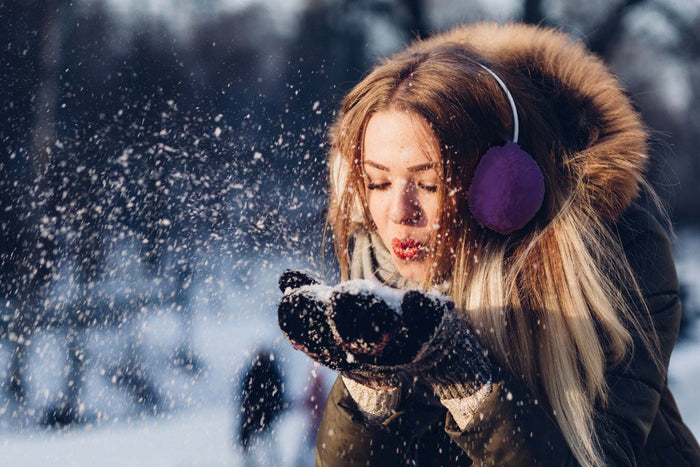 young woman wearing ear muffs blows snow from hands