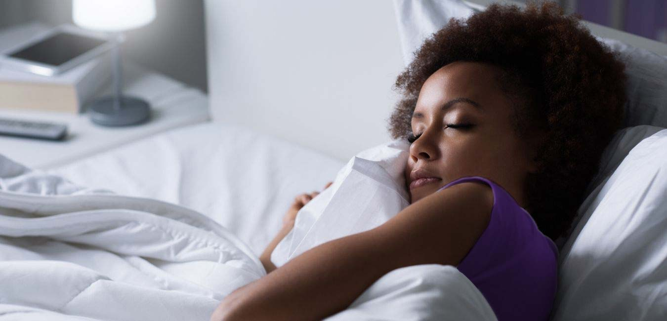 woman in purple shirt sleeps in bed with white sheets