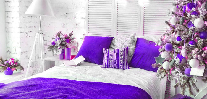 guest bedroom decorated for the holidays with purple accents