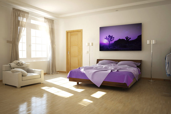 king size bed with purple sheets in large bedroom; sunlight shines in window reflecting on hardwood floors