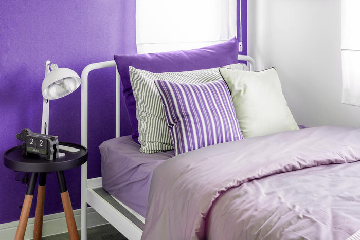 Single Twin bed made up with purple accent pillows