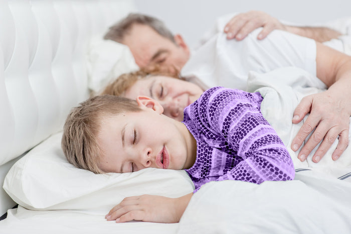 man, woman and child sleep in a row in bed with white sheets