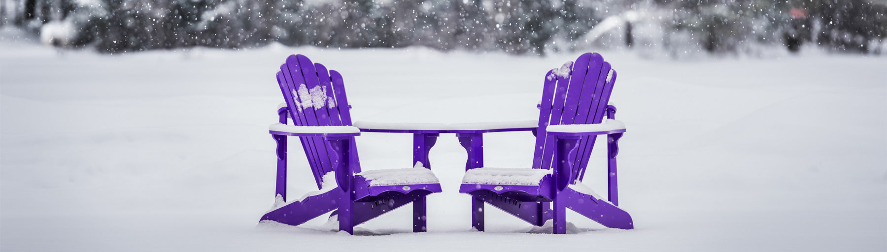 two purple adirondack chairs in snow covered yard