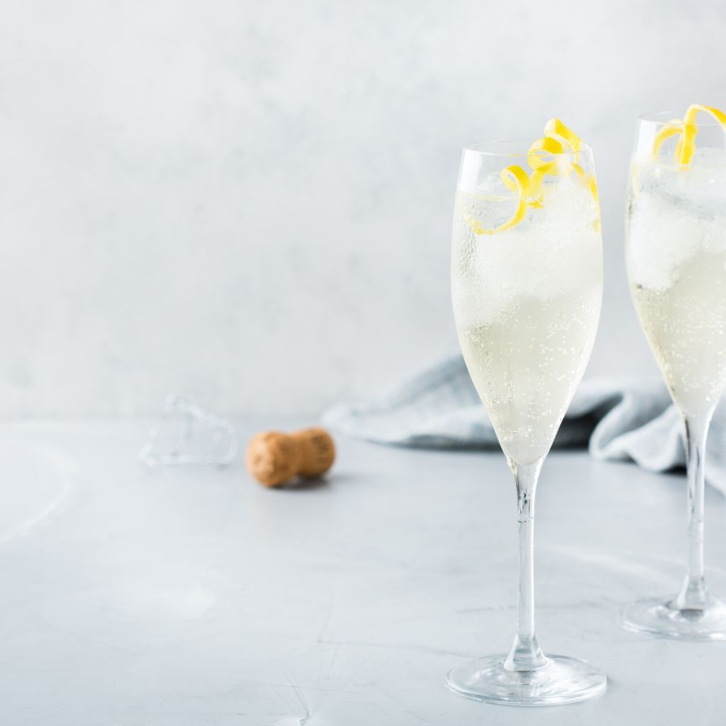 close up of two champagne glasses on a marble table