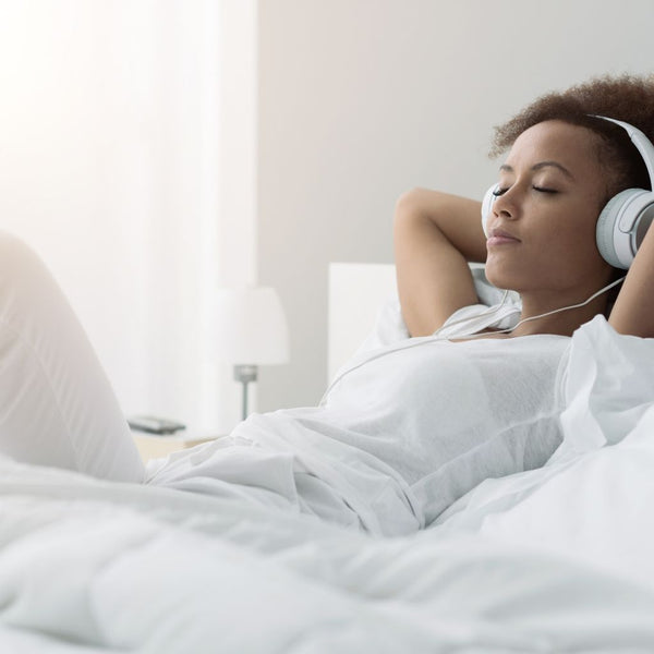 young African American women laying in bed listening to music on her headphones