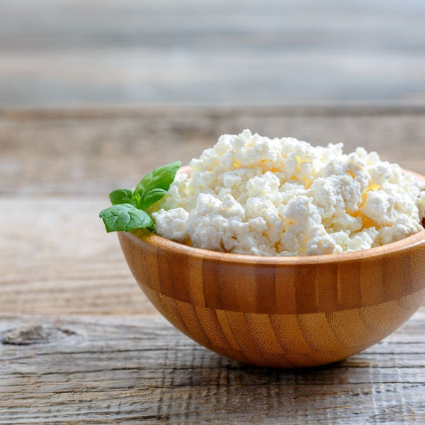 Close up of bowl of cottage cheese on a wooden table