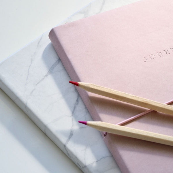 close up of a marble coloured notebook underneath a pink coloured notebook with two pencils on top of